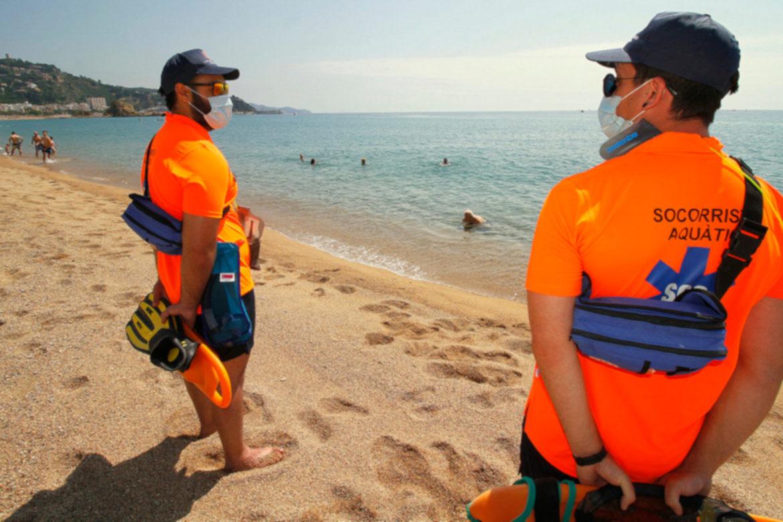 Dos socorristes a Blanes amb mascareta mentre alguns banyistes estan a l'aigua. Foto: Aj. Blanes