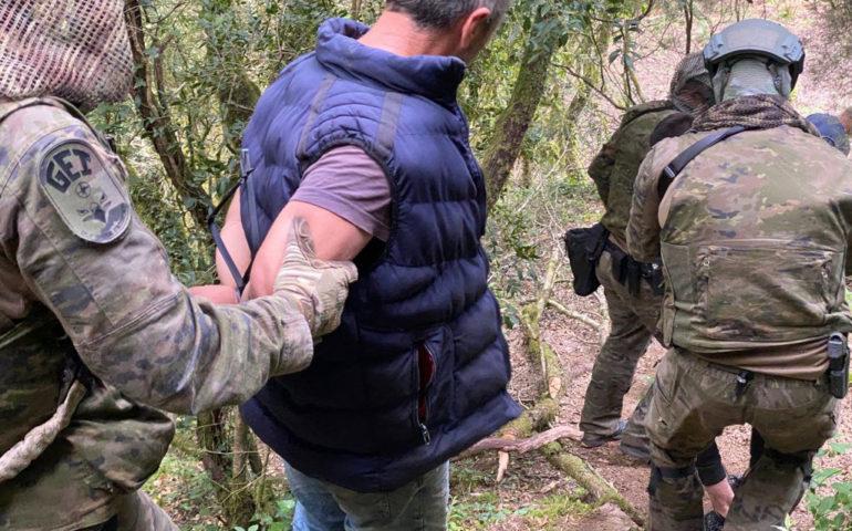 Un agent del GEI dels Mossos d'Esquadra acompanya una persona detinguda. Foto: Mossos d'Esquadra